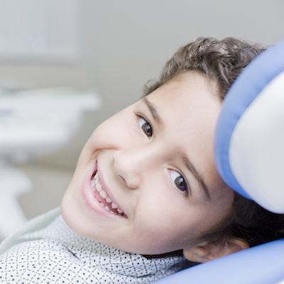 Young boy laying in a treatment chair looking back at the camera smiling