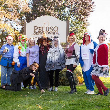 Our team of Peluso Orthodontics disguised outside our office, next to our sign