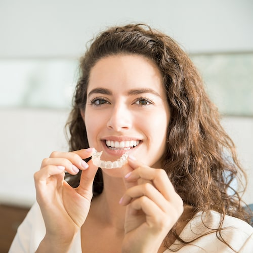 Woman with long curly hair smiling holding her Invisalign retainers in both hands