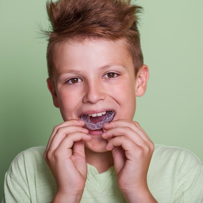 Boy wearing a green t-shirt putting his sports mouth gaurd in with both hands