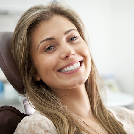 Young woman in a treatment chair smiling at the camera