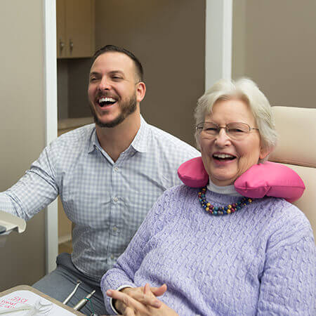 Dr. Peluso smiling with a patient at the chair